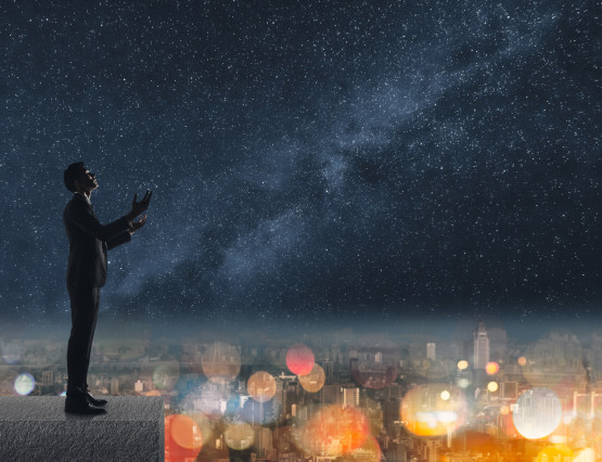 Silhouette of Asian businessman standing and praying at the roof under stars night in city.