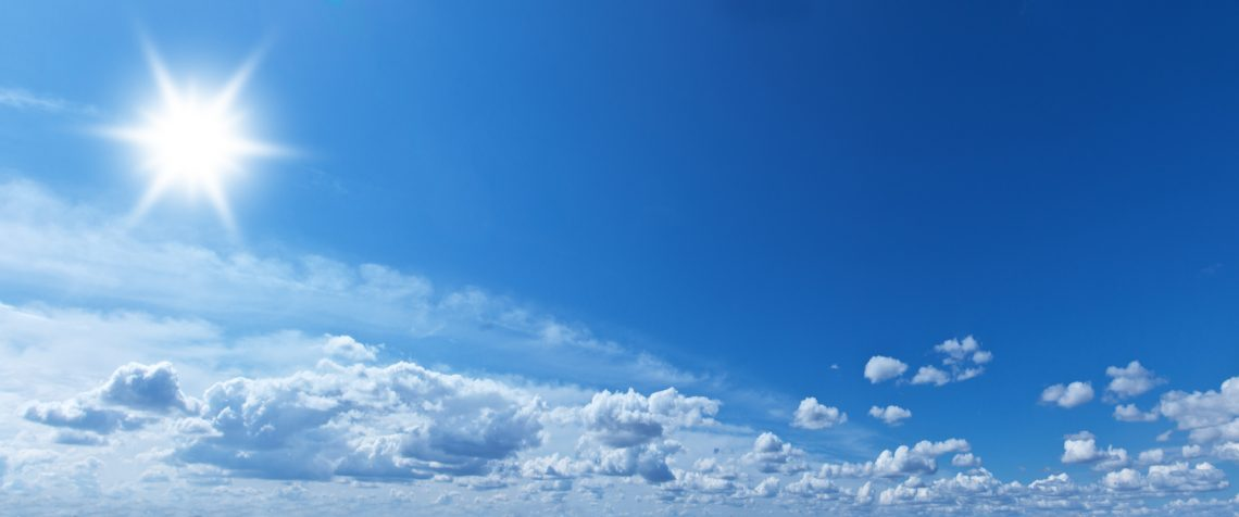 White heap clouds and bright sun in the blue sky at the summer day.