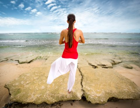 Asian woman doing yoga on beach, sitting on rock in lotus position