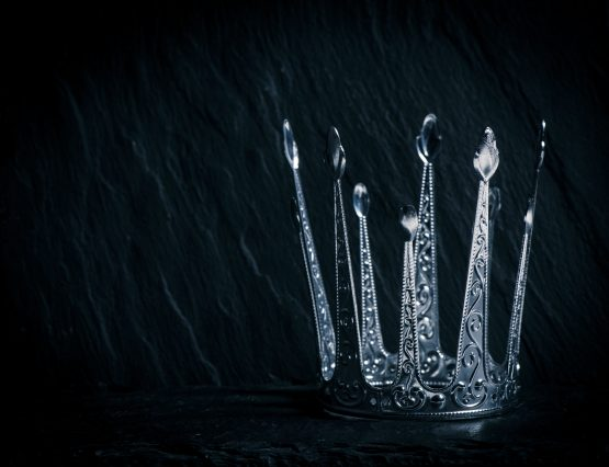 Royal crown on dark stone surface. Concept of wealth, success and kingdom.