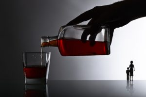 hand with bottle and a glass of whiskey